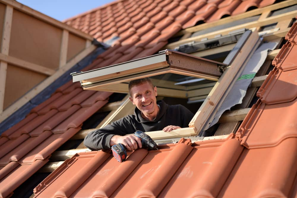 Roofer leaning out the roof window and looking at you