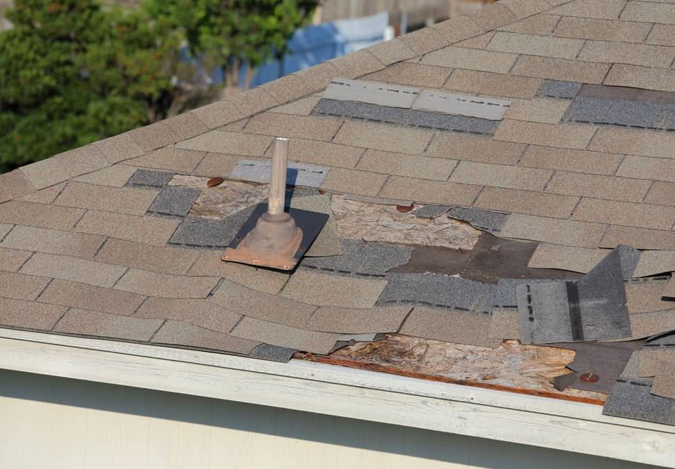 A close up view of shingles sticking out of a roof and other roof damage