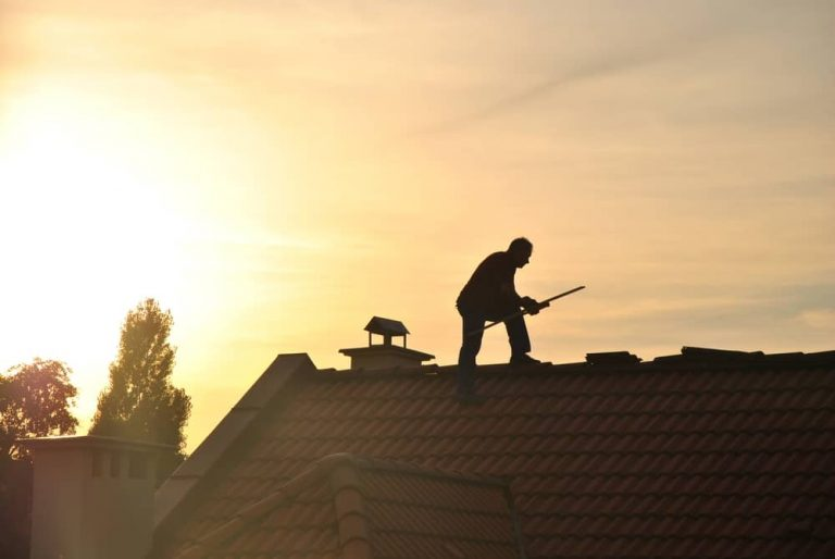 Man installing shingles on a roof at sunset