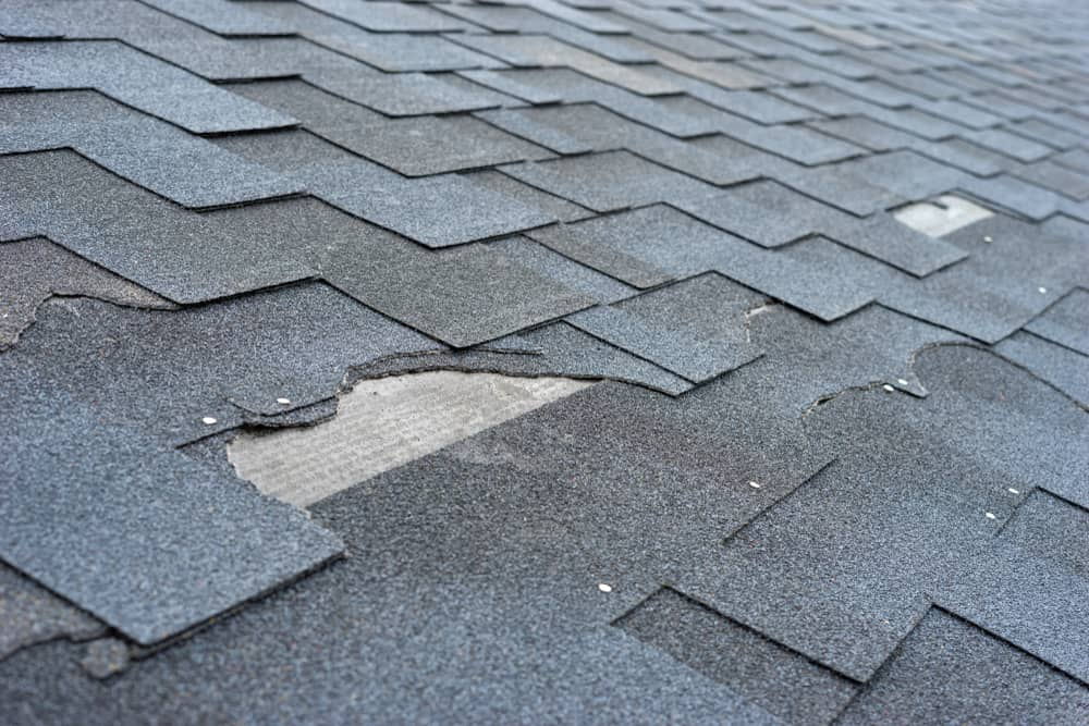 Roof of a house with broken and missing tiles