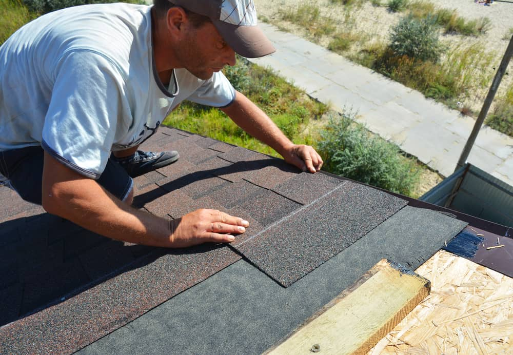 Roofer installing shingle in a roof