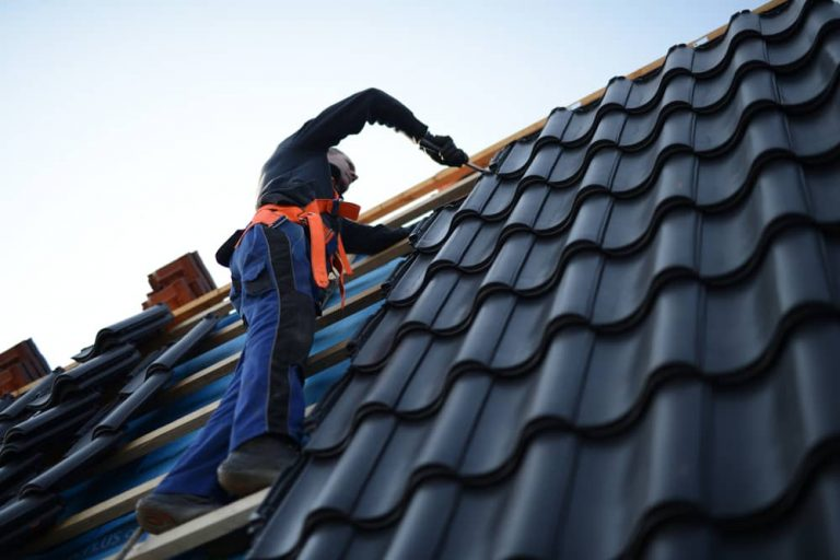 Roofer installing shingles in a roof