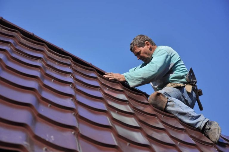 Roofer installing tiles in the roof