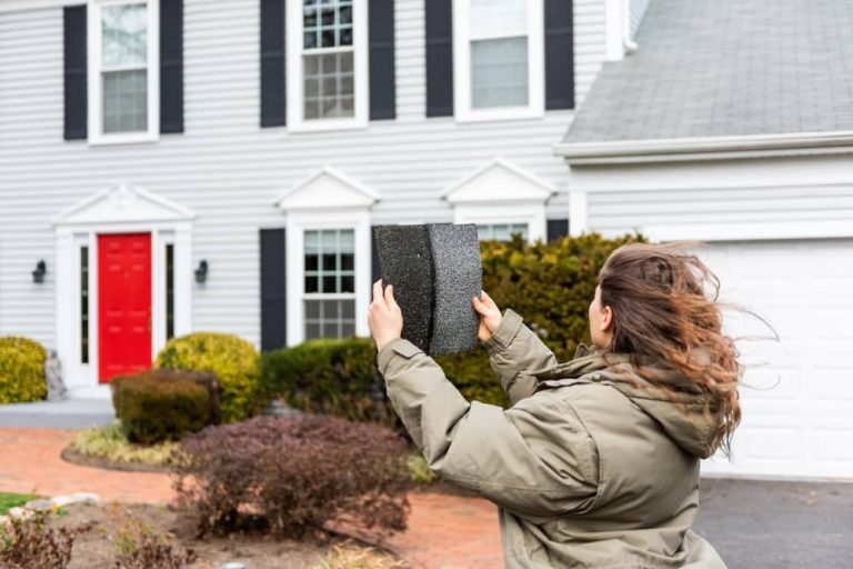 Young homeowner standing in front of house comparing the two tiles for her roof